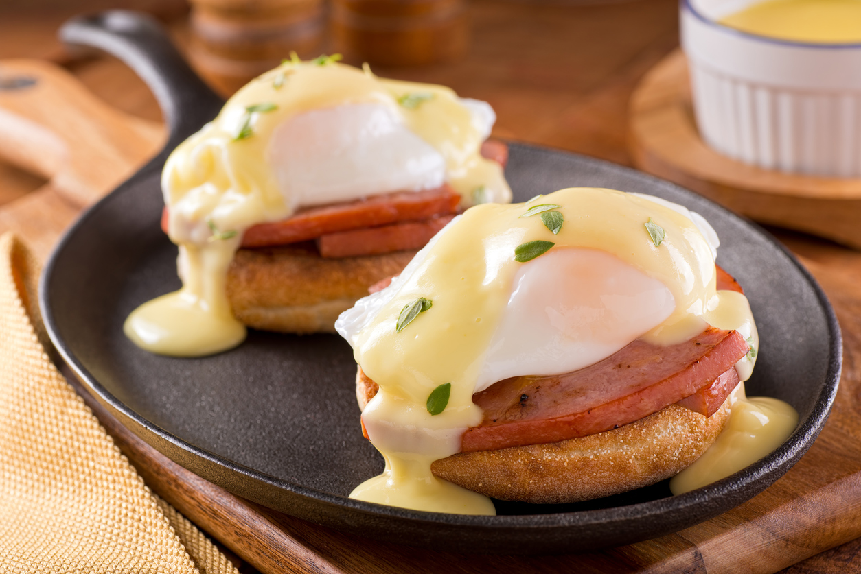 Eggs Benedict with Sliced Ham, Hollandaise Sauce, and Thyme Garnish