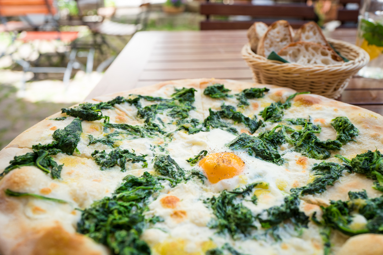 Oven-baked Pizza Topped with Cheese, Spinach, and Egg