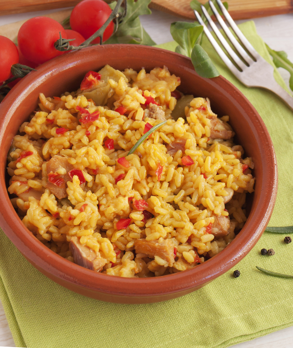 Clay bowl of chicken, chorizo and egg paella