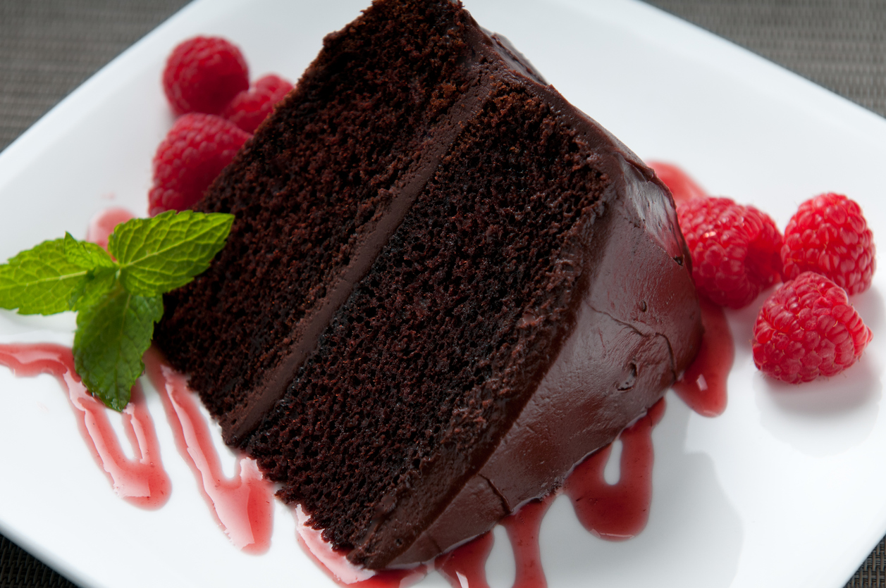 a piece of chocolate cake with chocolate icing, topped with fresh fruit.