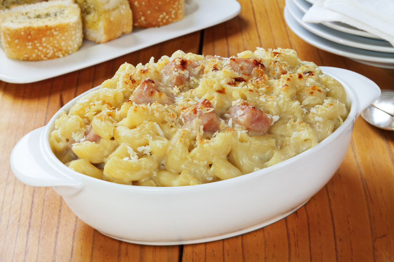 a bowl of baked macaroni and cheese topped with pieces of ham