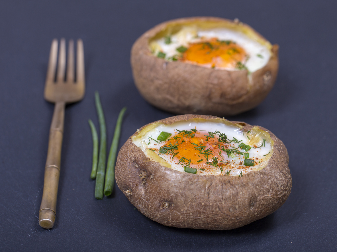 two baked potatoes stuffed with egg and cheese, topped with green onion