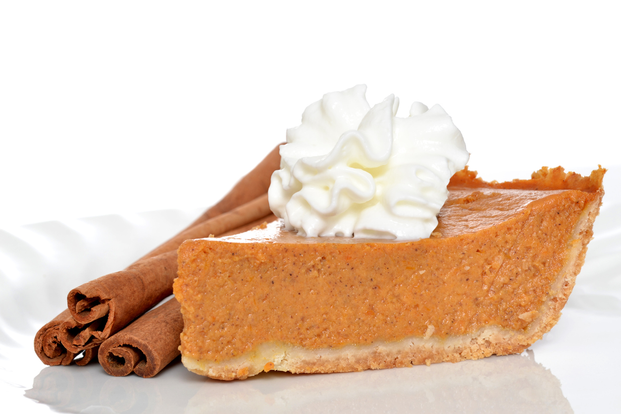 a slice of pumpkin pie with a graham cracker crust and whipped topping