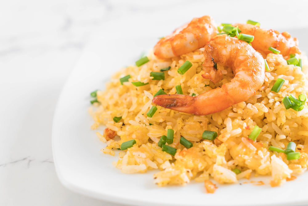 a plate of spinach and shrimp fried rice