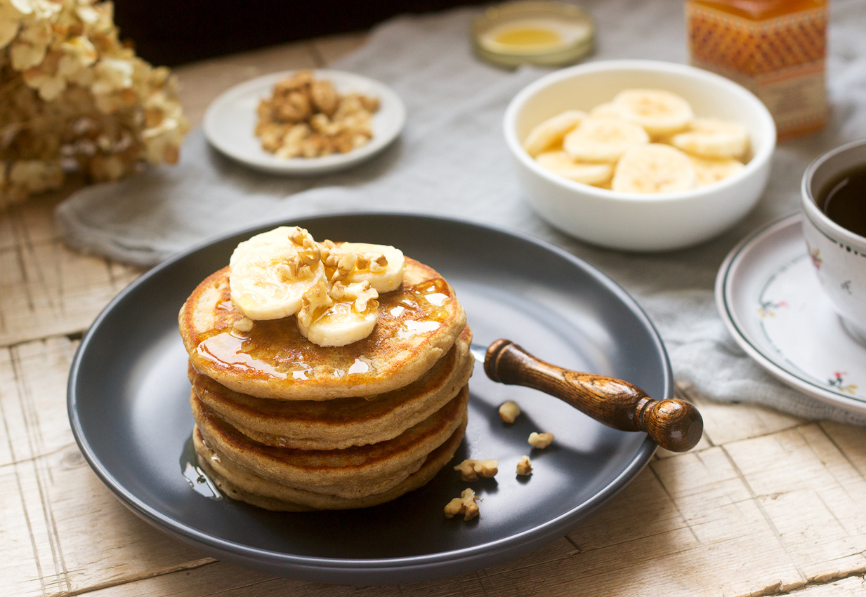 a plate of banana and egg pancakes topped with nuts