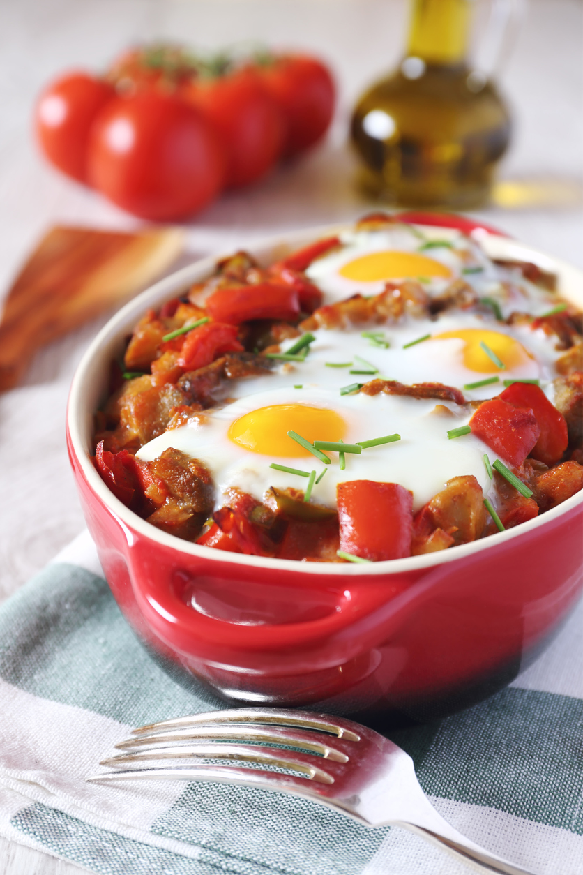 roasted ratatouille with eggs in a red dish